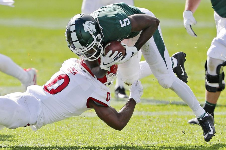 Michigan State wide receiver Jayden Reed  is tackled by Rutgers defensive back Christian Izien during their game at Spartan Stadium in East Lansing, on Saturday.