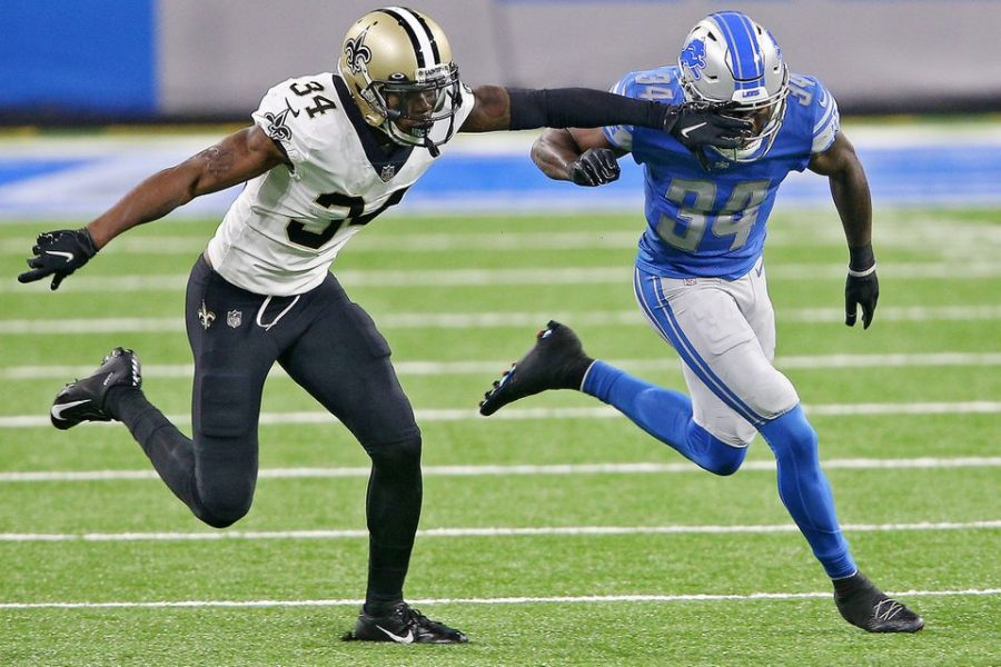 Detroit Lions cornerback Tony McRae and New Orleans Saints defensive back Justin Hardee Sr.  run up the field during their NFL game at Ford Field in Detroit, Michigan on Oct. 4