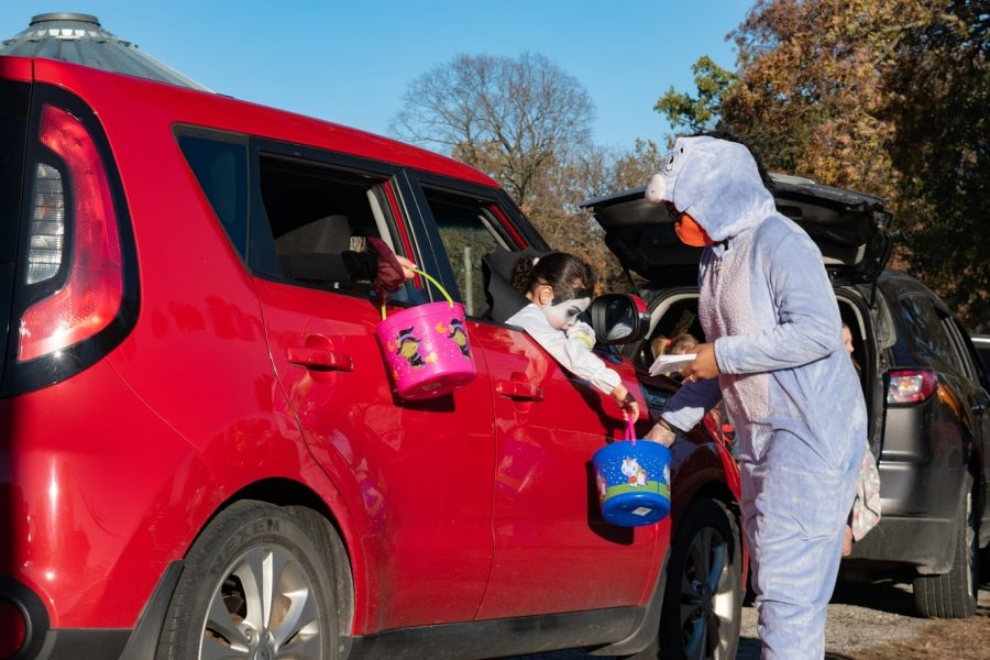 Children attending a drive-thru trick-or-treating event at the Champaign County Fairgrounds receive candy on Saturday. Many Champaign-Urbana residents celebrated Halloween with COVID-19 precautions this year.