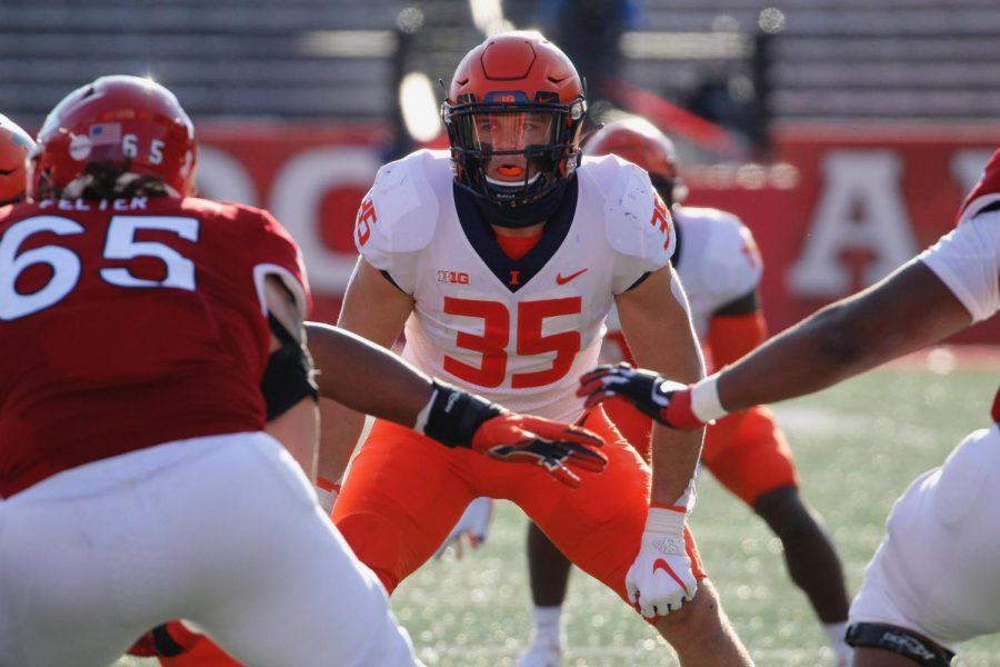 Senior linebacker Jake Hansen stands ready on the line of scrimmage during the game against Rutgers on Saturday. Hansen forced a turnover and intercepted the ball to help the Illini get their first win.