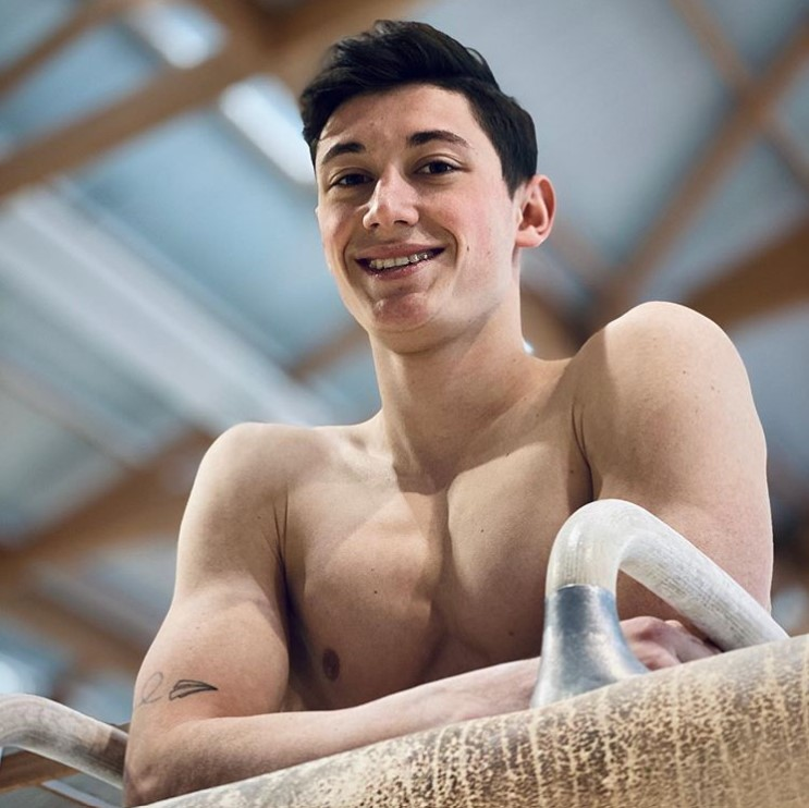 Graduate student Léo Valentin poses on a pommel horse. Valentin came to Illinois for gymnastics because he couldn't continue his studies and compete in his home country of France.