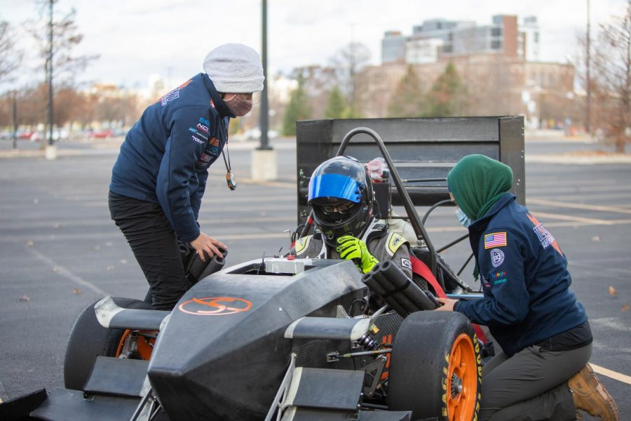 Salam Mulhem(right), senior in Engineering and President of Illini Motorsports works to prepare the car for a practice run. Salam is the team's first female president.