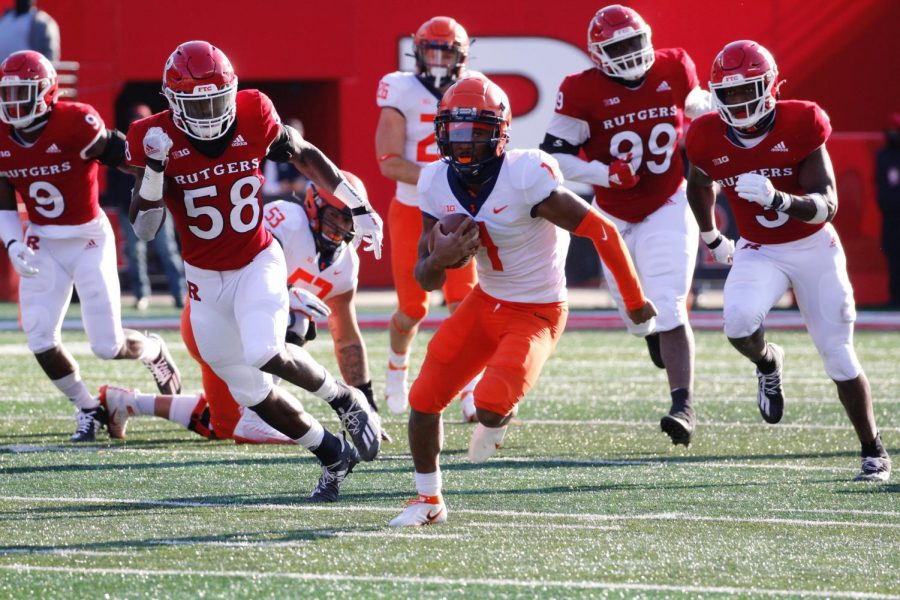 Quarterback Isaiah Williams runs through Rutgers defenders on Saturday. The Illini won 23-20.