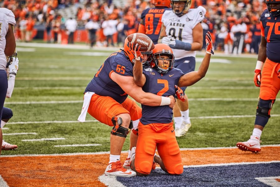 Illinois running back Reggie Corbin (2) and lineman Doug Kramer (65) celebrate after scoring a touchdown against Akron on Aug. 31, 2019. Kramer is set to return to play for the Illini this Saturday.