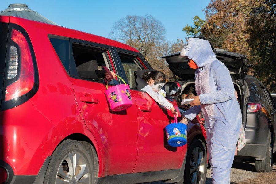 Local children receive candy at a drive-thru trick-or-treating event in Champaign on Oct. 30.