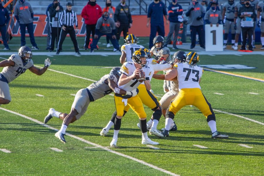 Illinois junior Khalan Tolson tackles Iowa quarterback Spencer Petras during the game between the two teams on Saturday. The Illini lost the game 35-21.