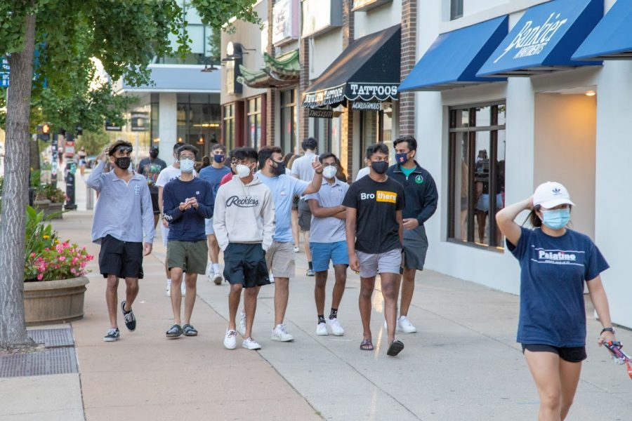 A group of students wearing masks walks down Green Street on Aug. 21.