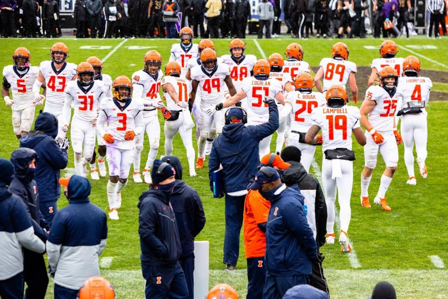 Players of the Illinois football team enter and exit the field between plays during the game against Northwestern on Saturday. The Illini lost the game 28-10.