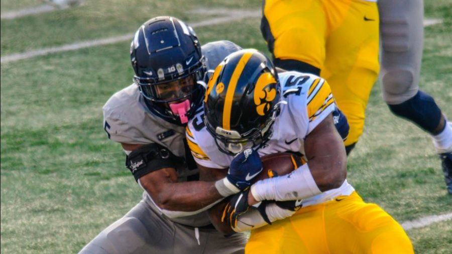 Senior Milo Eifler wraps up an Iowa ball carrier during competition. Eifler is leaving the Illinois football team to pursue opportunities in the NFL.