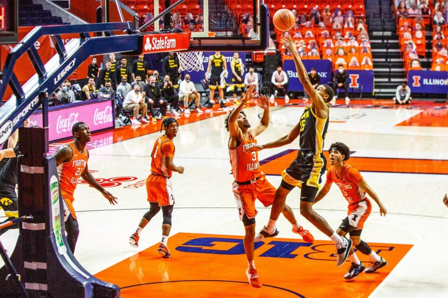 Jacob Grandison defends a shot in Illinois' game against Iowa on Friday. The Illini won 80-75.