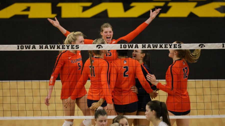 The Illinois volleyball team celebrates after scoring a point during the match against Iowa on Friday.