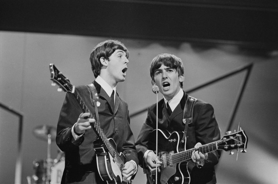 Beatles members George Harrison and Paul McCartney perform live. Columnist Noah argues Harrison helped spark Beatlemania in the United States with an early solo visit.