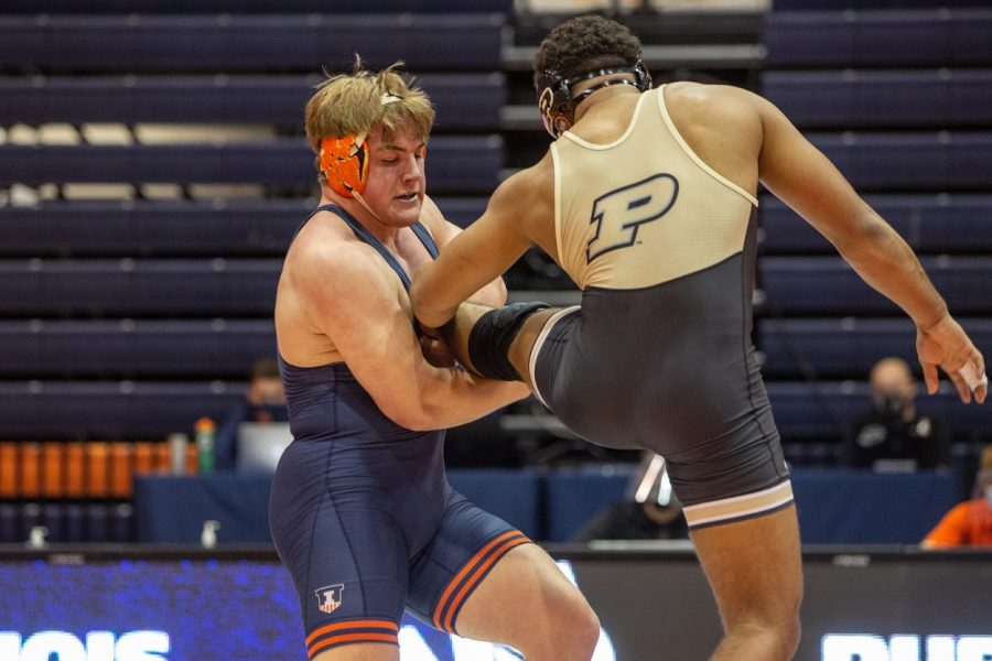 Sophomore Luke Luffman grabs the leg of his opponent during the meet against Purdue on Sunday. Luffman, along with Lucas Byrd and Dylan Duncan are undefeated so far this season.