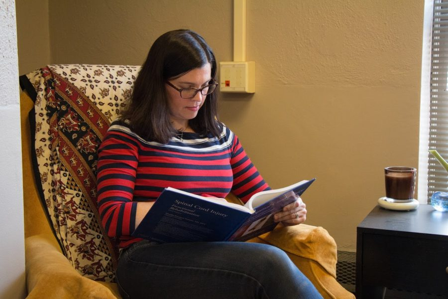 A woman sitting in a chair reads a book on April 12, 2018. Columnist Samuel suggests books to read in 2021.