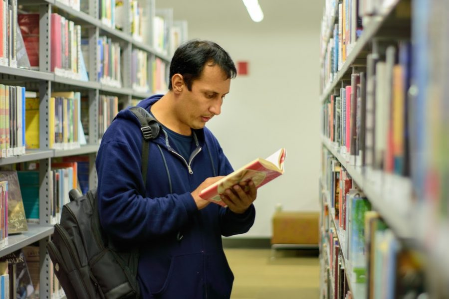 Hezbullah Akmal, 38, picks out a fiction novel at the Champaign Public Library on Nov. 5, 2018.