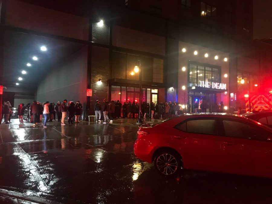 Residents of The Dean apartment building wait outside on Saturday night after a fire broke out inside the building. The cause of the fire is currently unknown.