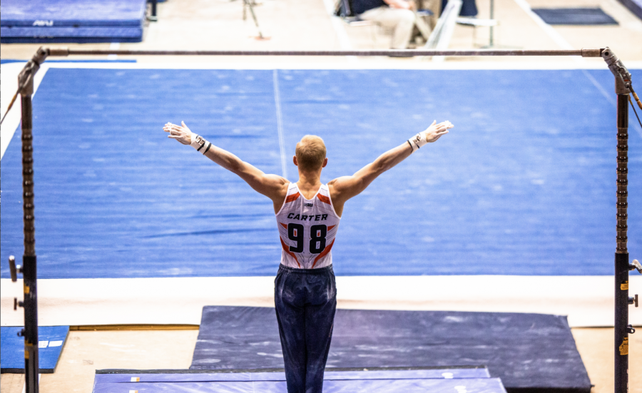 Junior gymnast Hamish Carter finishes his high bar routine and poses for the judges at Huff Hall on Saturday. Carter was named Male Gymnist of the week by the CGA and Big Ten.