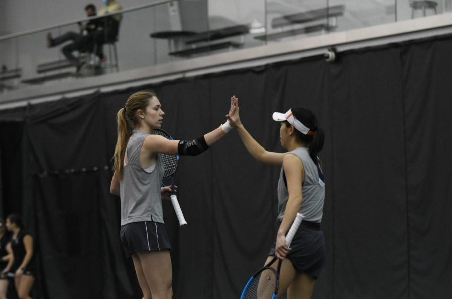 Members of the Illinois women's tennis team high five after scoring a point during the Purdue invite this weekend.