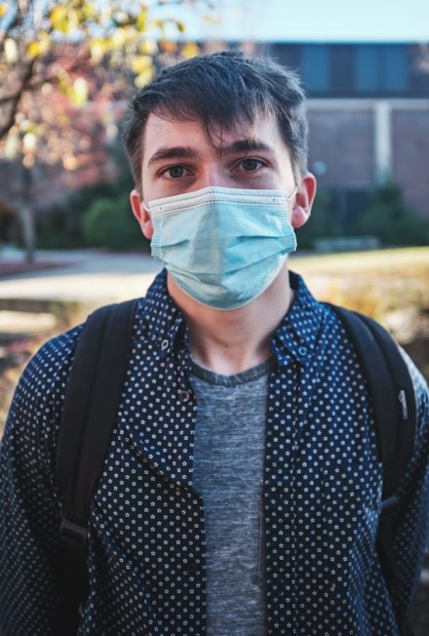 Junior Colin Heeneman waits in line to vote on Nov. 3. Heeneman is wearing a surgical mask, which according to a recent study, is the best type of mask to wear to be heard clearly.