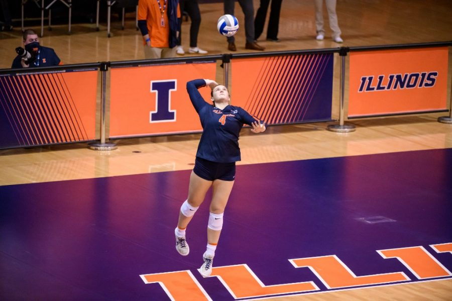 Senior setter Kylie Bruder rises up to serve during a game against Wisconsin at Huff Hall on Jan. 29. Bruder has overcome many challenges to become one of the team's star players this season.
