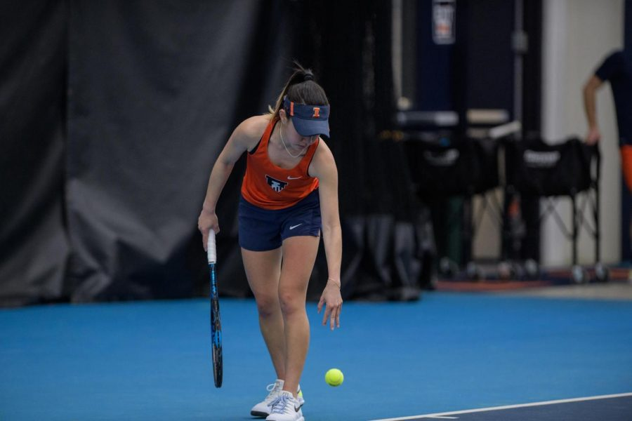 An+Illinois+women%27s+tennis+player+bounces+the+ball+before+serving+during+competition.+The+team+fell+to+Northwestern+6-1+on+Sunday.