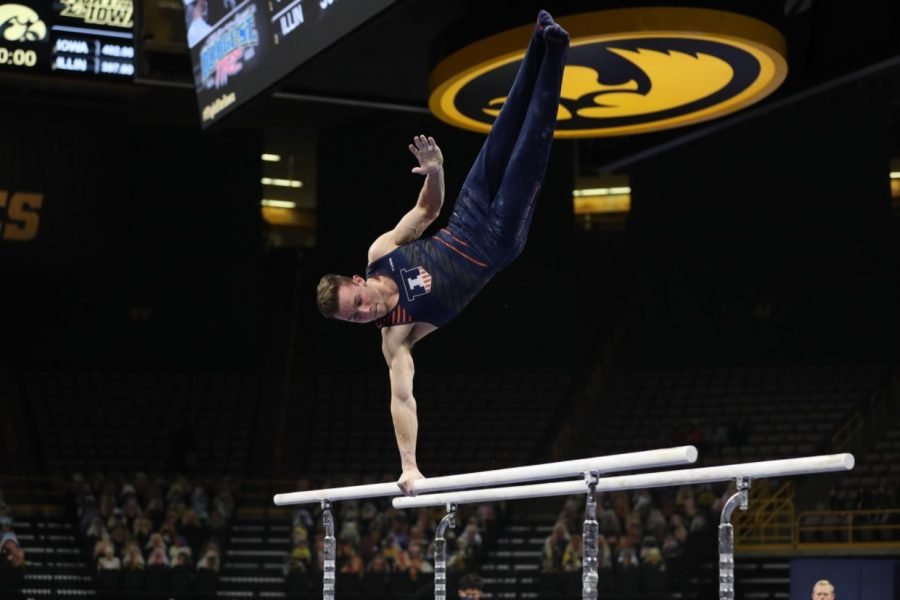 Junior Michael Fletcher performs his parallel bars routine during the meet against Iowa on Saturday. Illinois fell to Iowa 402 to 400.5.