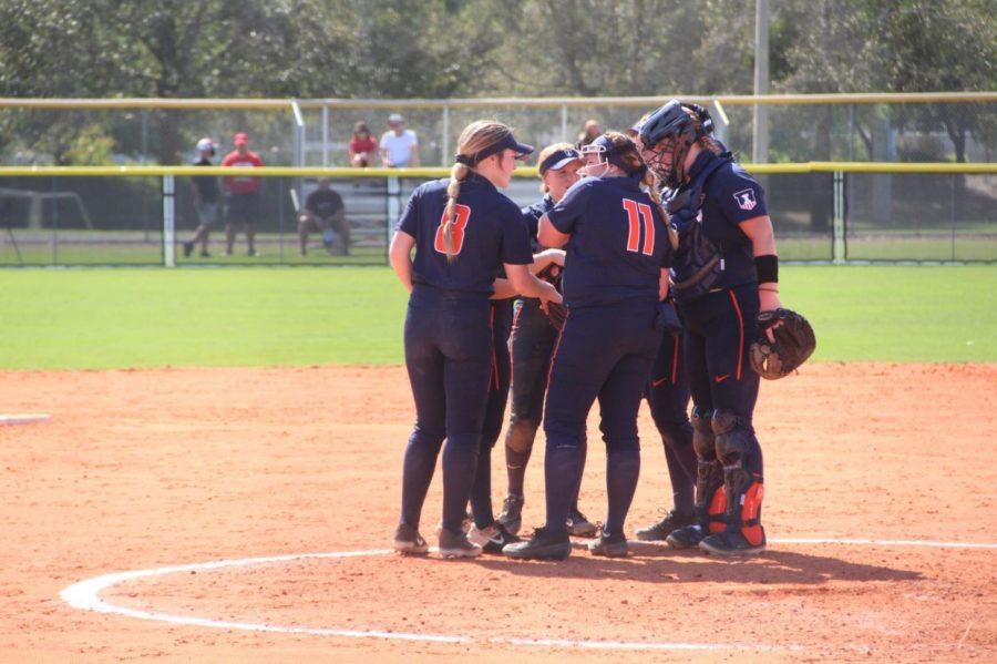 Members of the Illinois softball team gather at the mound to talk strategy during competition. The team won out in both games against Rutgers during a double-header on Friday.