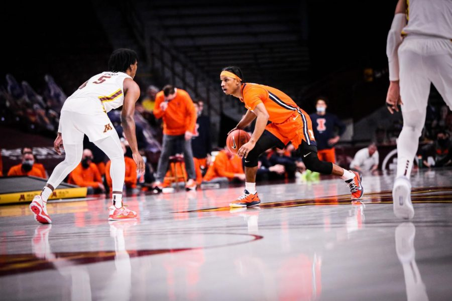 Trent Frazier dribbles the ball up the court during the first half of the game against Minnesota on Feb. 20.