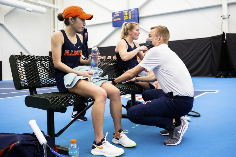 Women's head tennis coach Evan Clark checks on Emilee Duong and Sasha Belaya in between a match against Wisconsin on Feb. 26 at Atkins tennis Center. Clark was impressed by his teams performance against Iowa over the weekend despite losing to Nebraska on Sunday.
