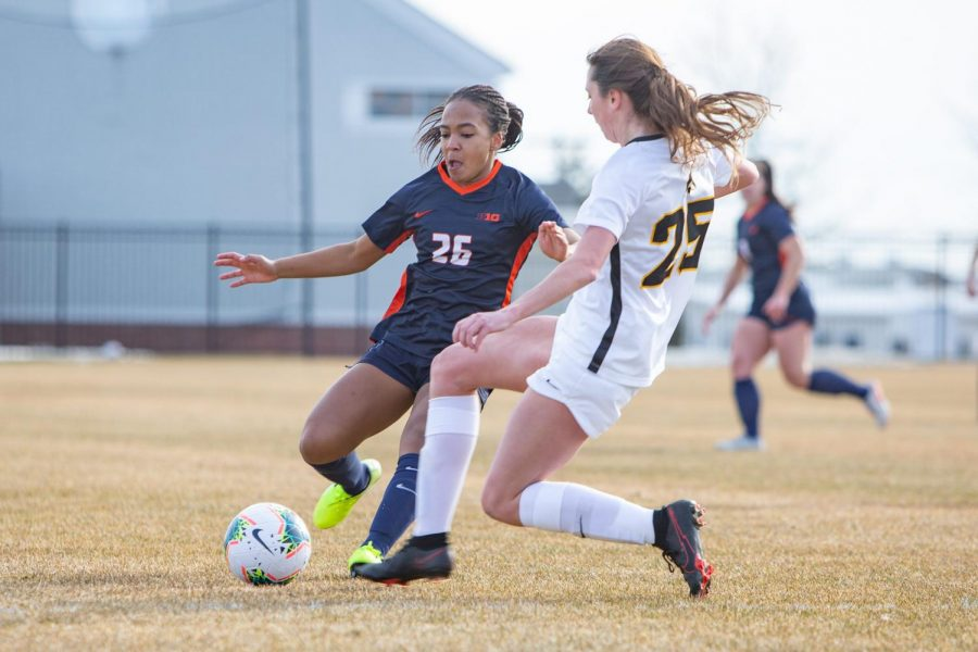 Sophomore Summer Garrison fights to keep possession of the ball in their game against Iowa on Feb. 26. The Illinois women's soccer team will play against the Spartans of Michigan State at 4PM CT today.