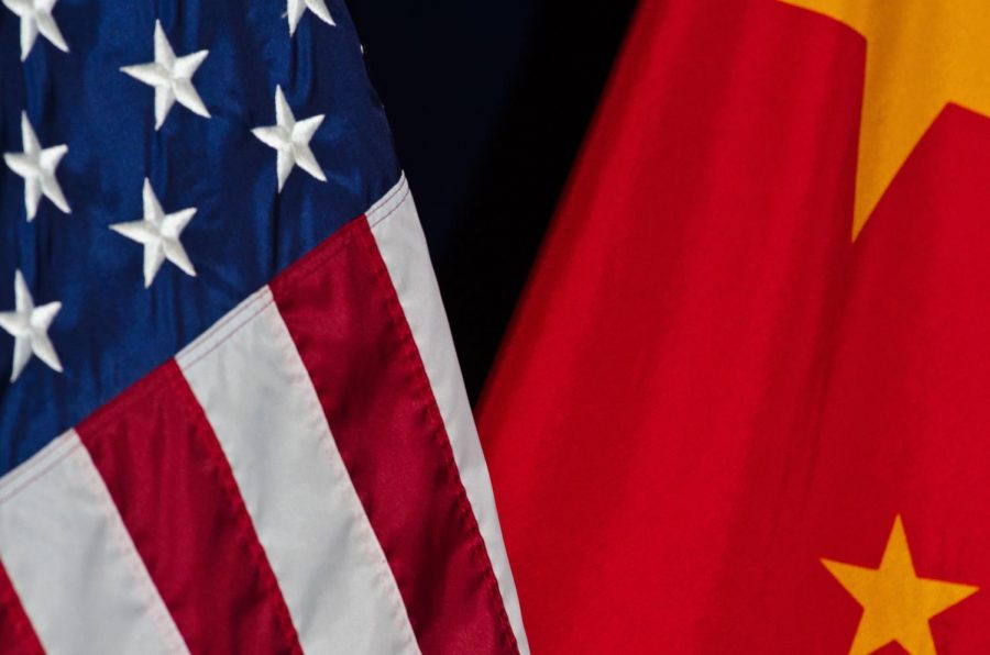 The Chinese and United States of America flags are draped over each other. Columnist Yuzhu Liu argues that international politics should require more cooperation between both parties.