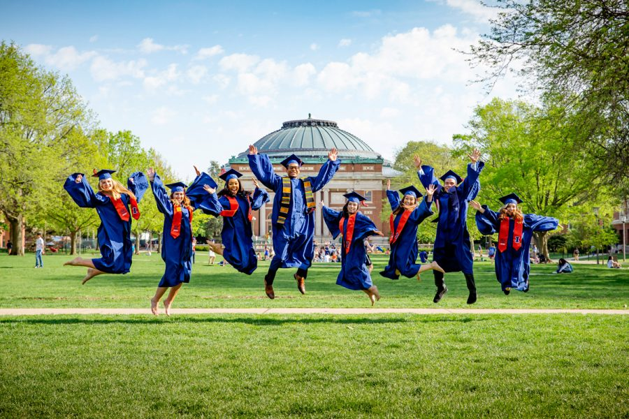 Illinois graduates jump in the air on the Main Quad after a previous year's commencement. The Illini Success team recently released a report detailing post-graduation pursuits of bachelor's degree recipients who graduated during the 2019-2020 academic year.