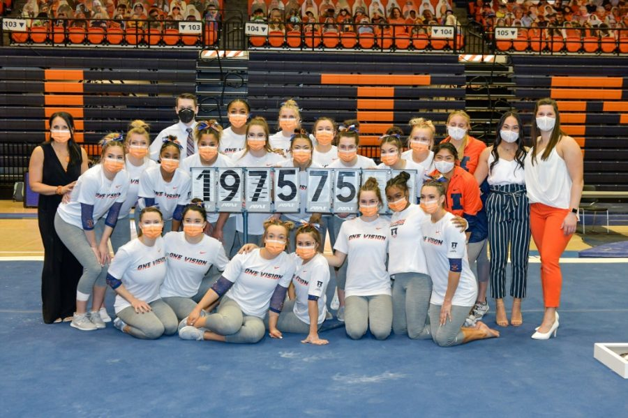The Illinois women's gymnastics team poses for a photo with a scoreboard showcasing their new all-around record. The team is using program records as motivation to compete to the best of their ability.