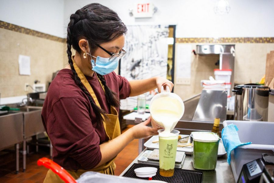 Freshman in Engineering Maia DeGuzman tops an avocado slush with cheese foam at Tenko Tea on Tuesday night. The shop has created many unique flavors to stay ahead of their competitors in the Champaign-Urbana area.