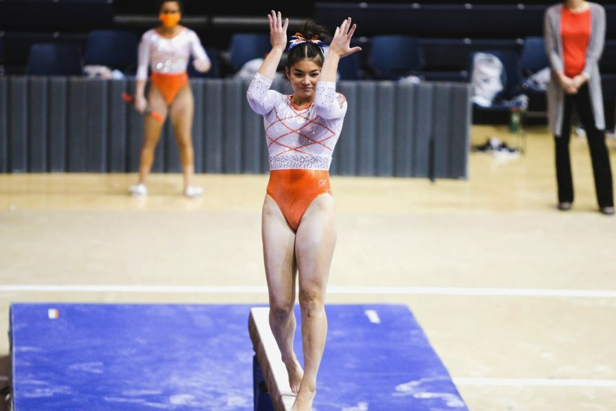 Junior Mallory Mizuki poses on the high beam during the meet against Iowa on Jan. 31. Mizuki continues to train and improve both mentally and physically.