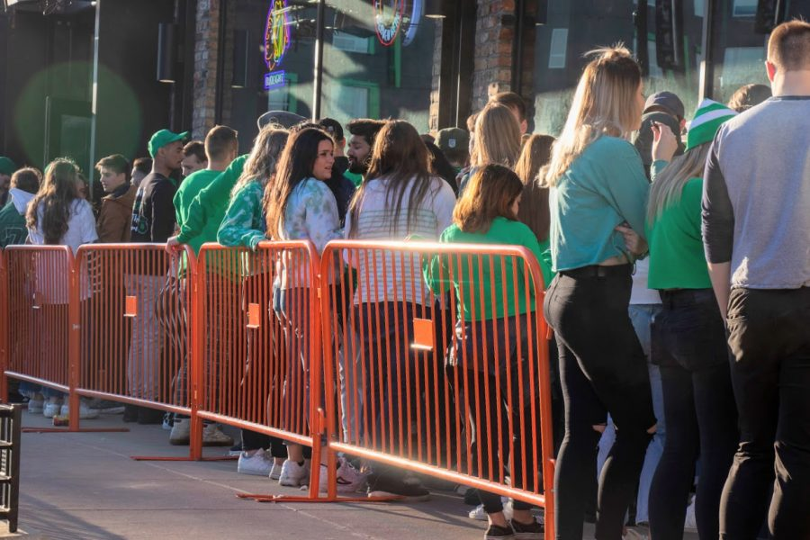 Bargoers wait in line outside of KAM's during Unofficial on March 6, 2020. The COVID-19 pandemic will likely severely limit the activities surrounding Unofficial this year.