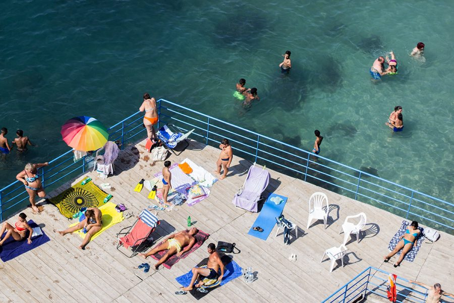 A group of people sunbathe on a platform extending into the Bay of Naples in Sorrento, Italy on July 31, 2018. Columnist Noah Nelson argues that University students require a spring break despite having theirs canceled for reasons related to Covid-19.