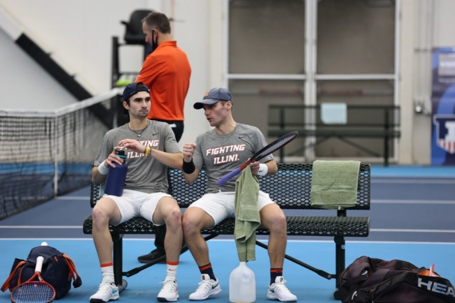 Senior Zeke Clarke and redshirt freshman Alex Bancila speak between games during the match against Penn State on Feb. 19. The Illinois men's tennis team captured two road wins against Minnesota and Wisconsin this weekend.