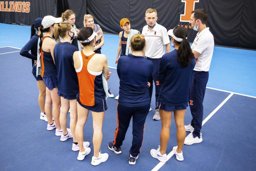 The Illinois women's tennis team huddles around head coach Evan Clark before their singles matches against Wisconsin on Feb. 26. The Fighting Illini are hosting Purdue and Indiana this weekend at Atkins Tennis Center.