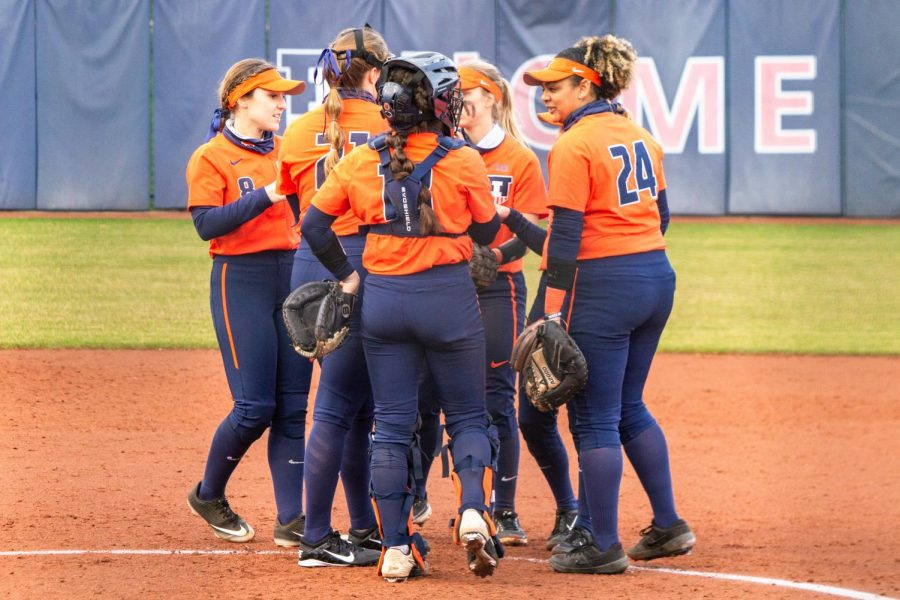 The Illinois women's softball team huddles up during a game against Minnesota on friday. The team lost their first three games against minnesota, but powered through and won 8-0 on Sunday.