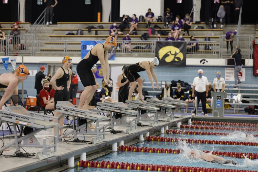 Junior Abigail Cabush prepares to dive in during a relay race at competition. The Illinois swim and dive team placed 12th at the Big Ten Championships this week.