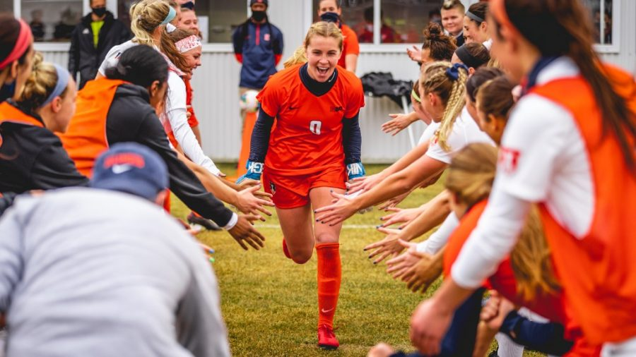 Sami Sample runs through a tunnel of teammates before a game against Penn State on Feb. 28. Sample was recently awarded player of the week by College Soccer News.