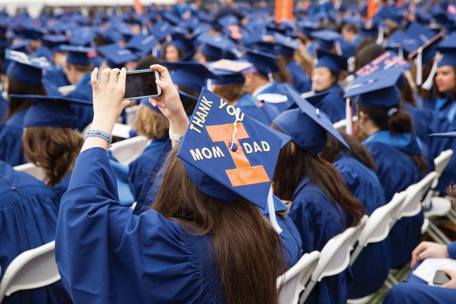 A University of Illinois graduate takes a photo while seated at the May 16, 2015 Commencement at Memorial Stadium. The University will be conducting a hybrid of virtual and in-person private stage crossing experiences for 2020 and 2021 graduates this May.
