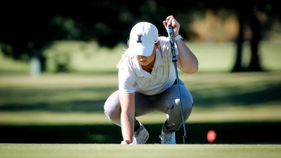 Senior Tristyn Nowlin crouches down to observe a putt during a golf match. Nowlin and Crystal Wang tied for eighth place at the Briar's Creek Invitational in South Carolina and the Illini came in 11th place overall.