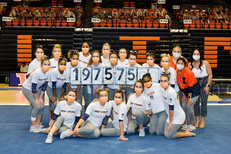 The Illinois women's team poses with its final score at Huff Hall on March 13. The Illini beat the Golden Gophers on Senior Night, and the score was the highest in program history.