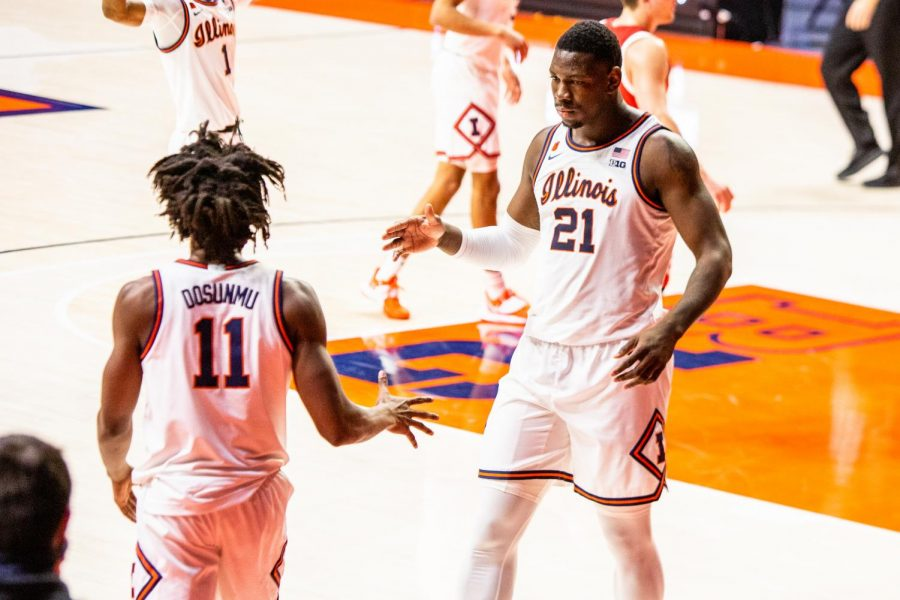 Sophomore Kofi Cockburn and Junior Ayo Dosunmu prepare for an embrace during the game against Wisconsin on Feb. 6 . Both Cockburn and Dosunmu must soon decide whether to declare for the NBA draft or return to Illinois for another season.