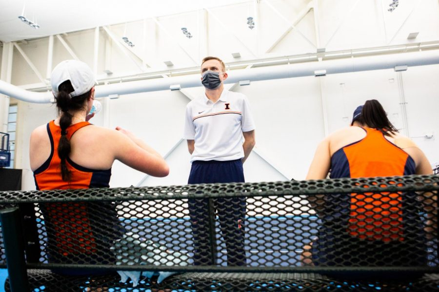 Head coach Evan Clark waits for Kate Duong and Ashley Yeah to cool down before giving them some tips during their doubles match against Wisconsin Feb. 26. Clark has transformed the program since taking over as head coach in 2016.