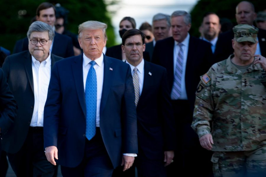 Former US President Donald Trump walks with his team from the White House to visit St. Johns Church after the area was cleared of people protesting the death of George Floyd on June 1 in Washington, DC. Columnist Dennis Austin argues that Trump promotes white supremacy and encourages bad behavior.