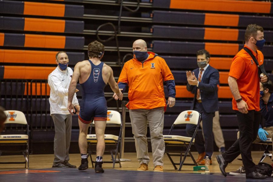 Illinois head wrestling coach Jim Heffernan shakes the hand of a wrestler after a match against Purdue on Jan. 22. Heffernan has just announced his retirement after 29 years in the Illinois wrestling program.