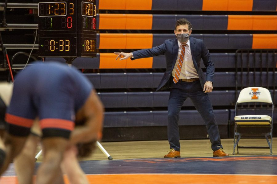 New head wrestling coach Mike Poeta instructs a wrestler from the sidelines during the meet against Purdue on Jan. 22. Poeta was previously the assistant coach for four years but was promoted after previous head coach Jim Heffernan retired.